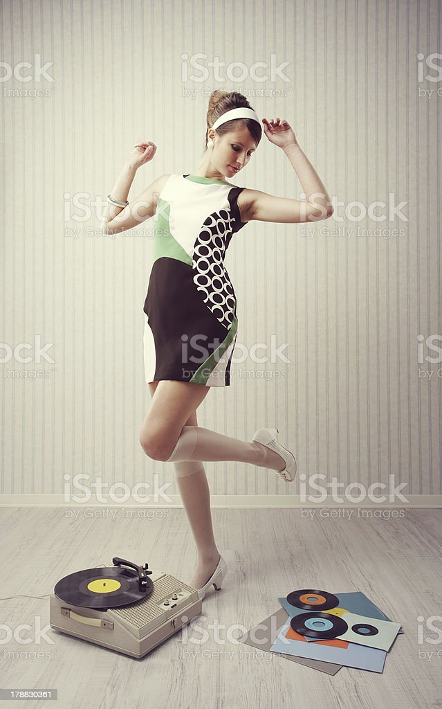 Woman in 50's attire dancing with a record player & records stock photo