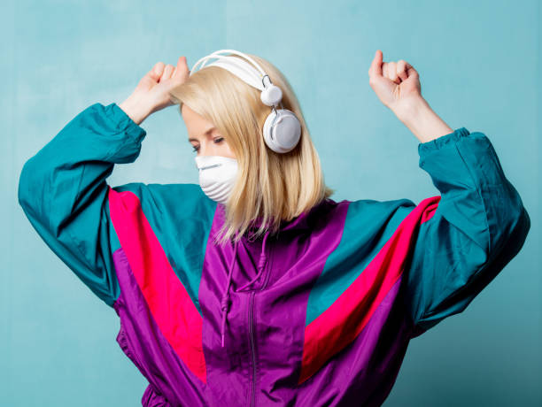 woman in 90s clothes and face mask with headphones stock photo