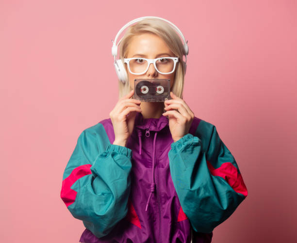 woman in 90s clothes with headphones and audio cassette stock photo