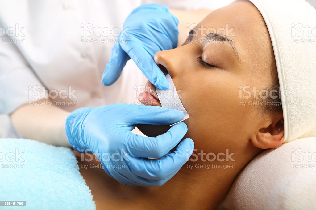 Woman in a beauty salon waxing during surgery stock photo