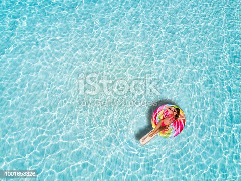 Beautiful woman in a bikini enjoys the tropical sun of the Maldives on a lollipop shaped float over the turquoise colored waters