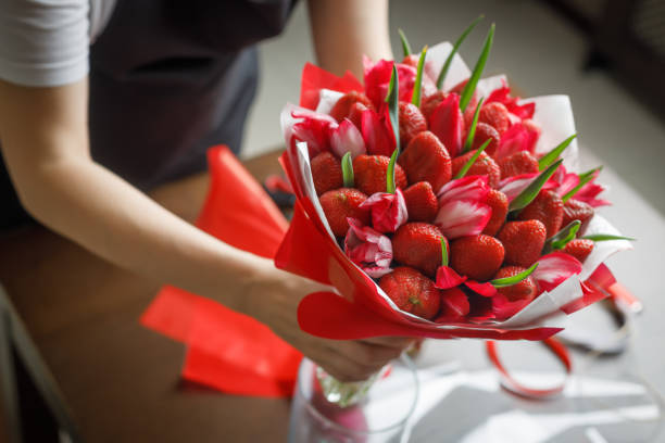 Woman in a black apron puts in a vase a beautiful original bouquet of tulips and strawberries stock photo