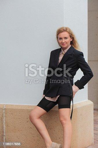 Woman in a black blazer outdoors