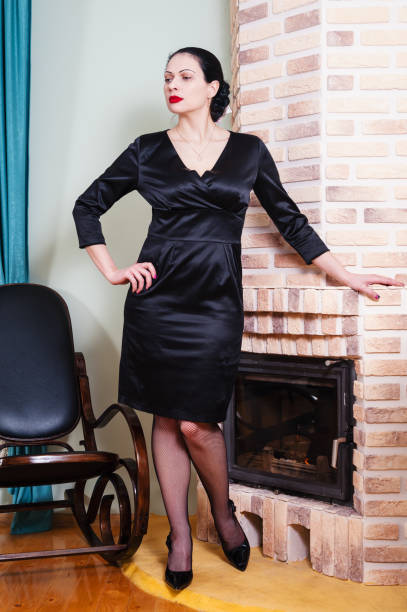 woman in a black evening dress standing near fireplace - stocking solo tube stock-fotos und bilder