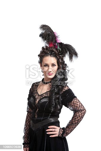 Lovely young brunette woman with feathers in her hair in fabulous robes dressed and dancing and posing in the studio