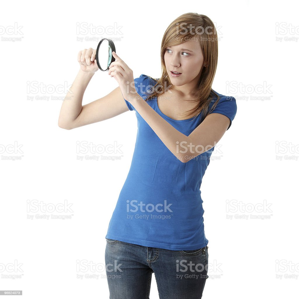 A woman in a blue shirt using a magnifying glass royalty-free stock photo