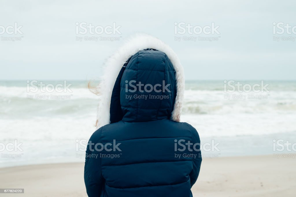Woman in a blue winter jacket with a hood stands on the winter beach and looking at sea royalty-free stock photo