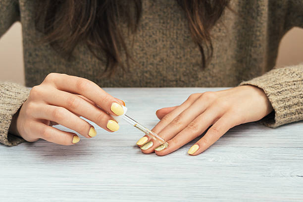 woman in a brown sweater with yellow manicure applying cosmetic - cuticle stock pictures, royalty-free photos & images