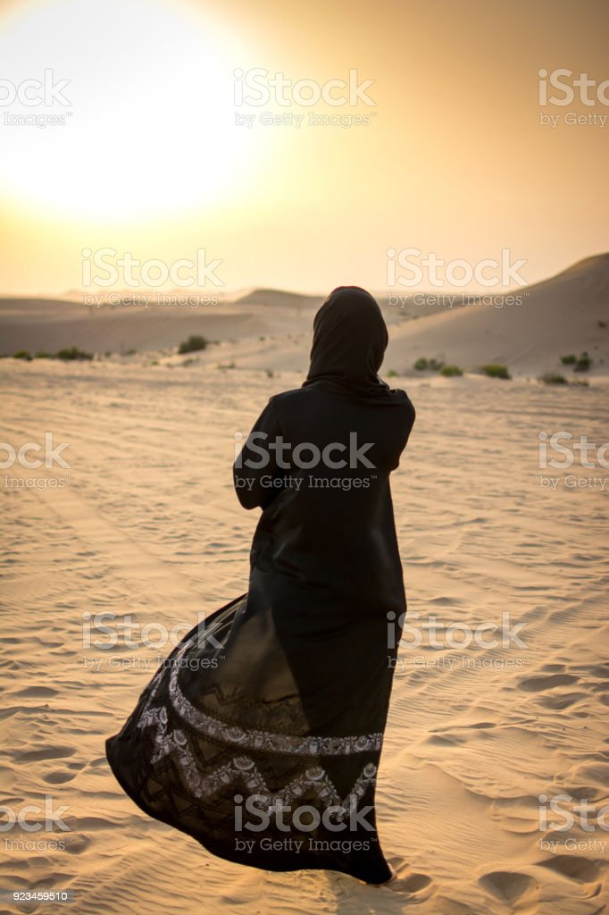 Woman in a burka Burqa walking over a middle eastern desert during sunset. stock photo