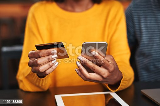 Close-up of a young woman in cafeteria using mobile phone and credit card for shopping online