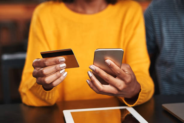Woman in a cafe shopping online with credit card Close-up of a young woman in cafeteria using mobile phone and credit card for shopping online home shopping stock pictures, royalty-free photos & images