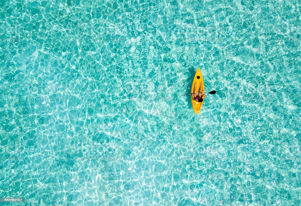 Mujer en una canoa sobre las aguas color turquesa, tropicales - foto de stock