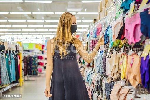 istock A woman in a clothing store in a medical mask because of a coronovirus. Quarantine is over, now you can go to the clothing store 1220917389