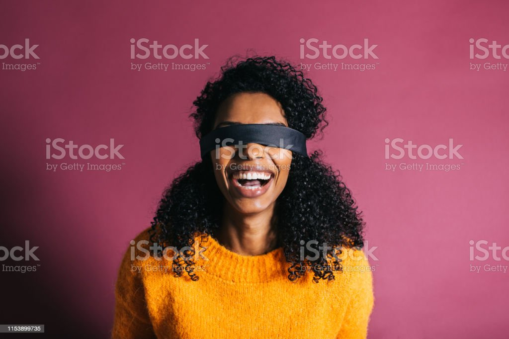 Woman in a colorful background Beautiful black woman wearing a orange jumper looking at camera while making funny face expressions in a pink background Adult Stock Photo