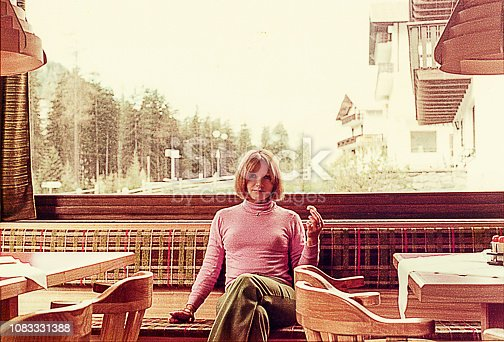 vintage photo of a woman sitting on a coffee shop on a winter cold day.