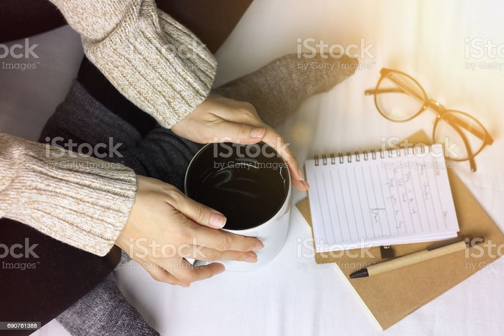 Woman in a cozy sweater holding a cup of hot drinks, Working and reading a book in a lazy day, Winter morning at home in bed, Feeling warm concept.