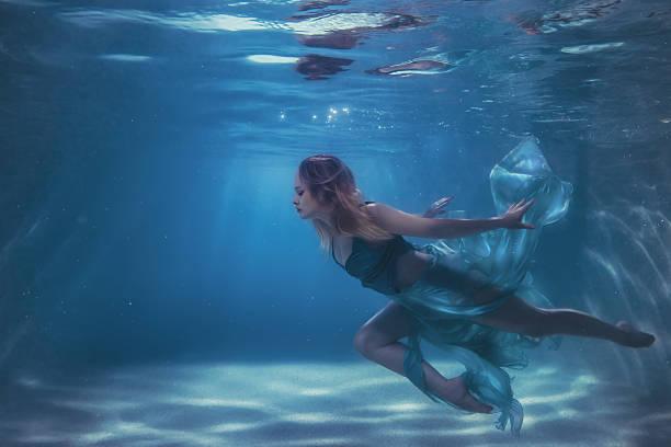 woman in a dress dives into the water. - meerjungfrau kleid stock-fotos und bilder