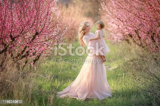 A woman in a dress like a pink bride in nature in the garden with a baby in her arms.