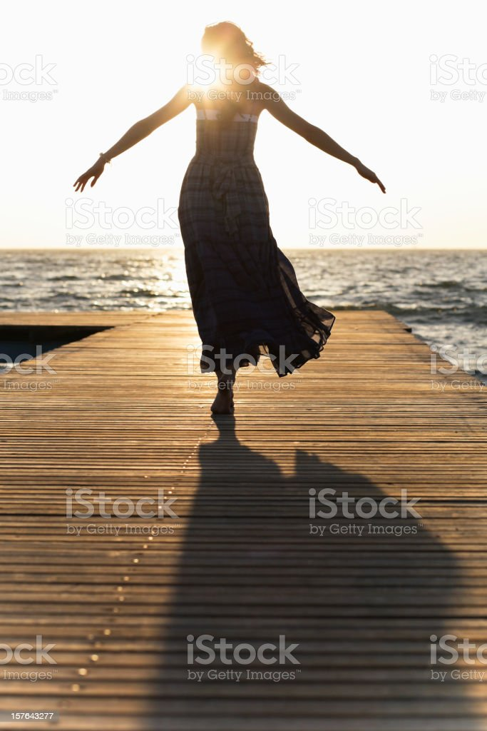 A woman in a dress on a dock with her arms spread stock photo