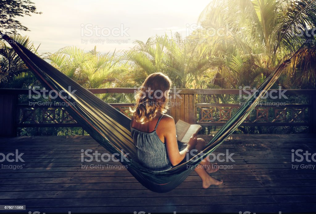 woman in a dress reading book in a hammock in the jungle at sunset. stock photo