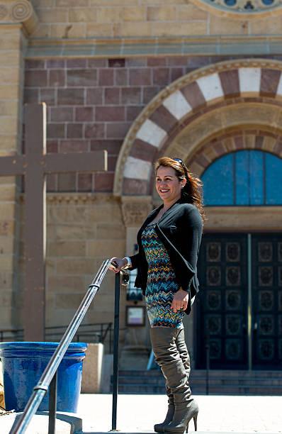 Mulher em um vestido suéter & em frente da igreja - foto de acervo