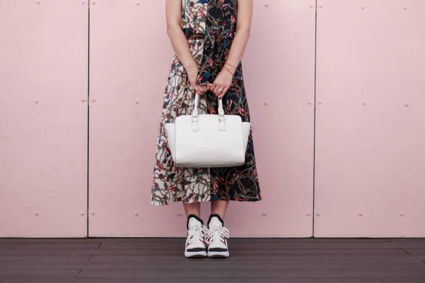 frau in ein modisches kleid mit einem weißen stylische tasche stand in der nähe der rosa wand. damen mode turnschuhe - vogue muster stock-fotos und bilder
