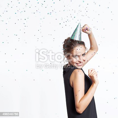istock Woman in a festive cap dancing and smiling 496346786