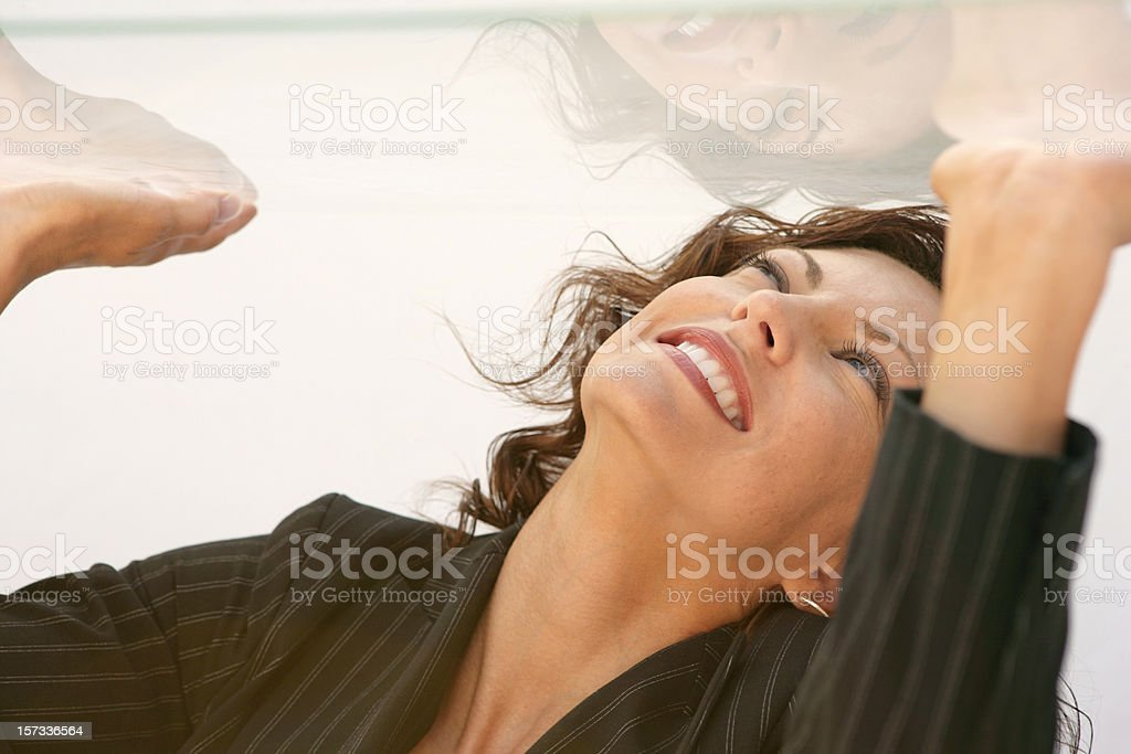 Woman in a glass box trying to get out by punching the roof  stock photo