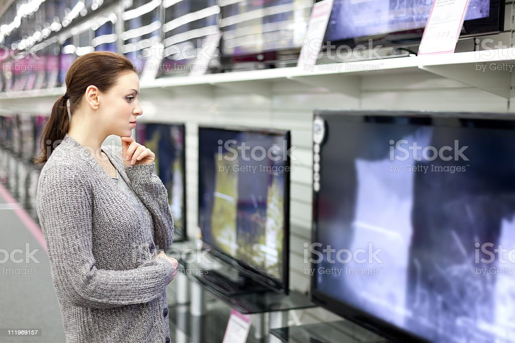 A woman in a gray cardigan looking at TV's in a shop royalty-free stock photo
