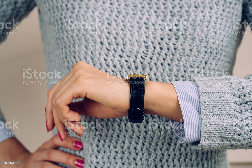 Woman in a gray sweater checks the time on watch stock photo