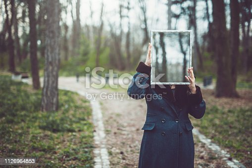 A woman in a green coat standing in a park area holding up a mirror that hides her face