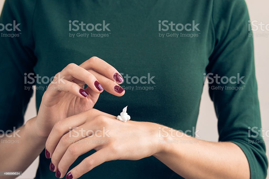 Woman in a green T-shirt applying hand cream stock photo