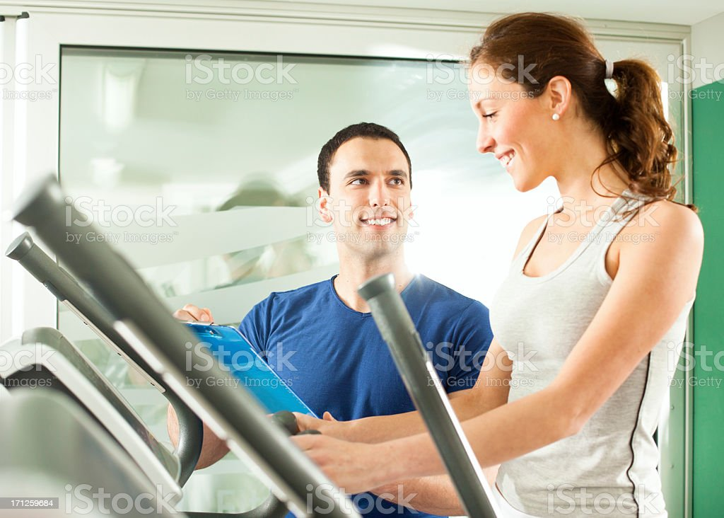 Woman in a gym with personal trainer. royalty-free stock photo
