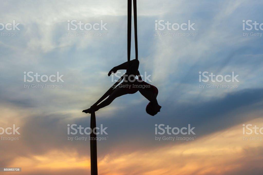 Mujer en una hamaca haciendo acrobacias. - foto de stock