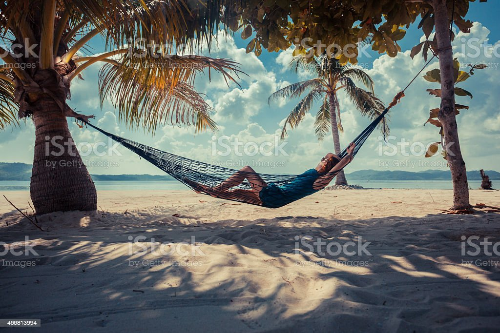 A woman in a hammock relaxing by the beach stock photo