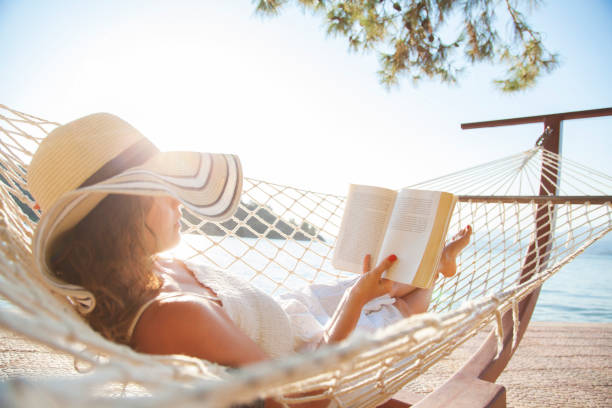 Woman in a hammock with book on holiday stock photo