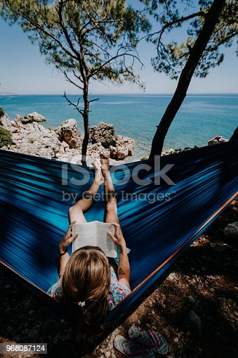 817409212 istock photo Woman in a hammock with book on holiday 968087124