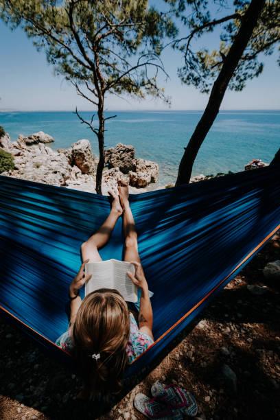 Frau in einer Hängematte mit Buch im Urlaub – Foto