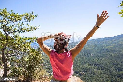 istock Woman in a hat looks at the panoramic view from the mountain to the sea and the forest. Tourist, trekking, travel. Active ecotourism, healthy lifestyle, adventure 1299046027
