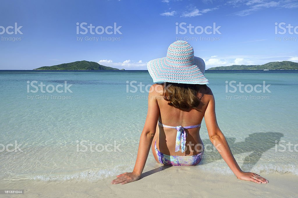 Woman in a hat sits back on the  beach sunbathing royalty-free stock photo