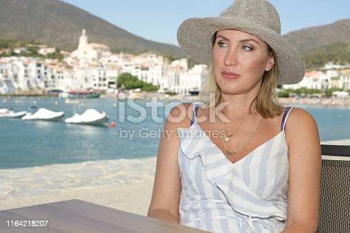 A woman in a hat sitting on a terrace on the promenade of a well-known Mediterranean town called Cadaqués with the village in the background. Vacation concept