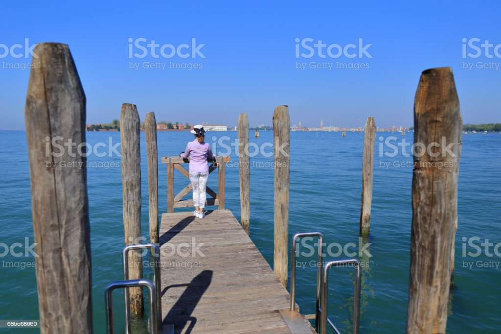 Woman in a hat stands leaning on balustrade and looks at the city of Venice royalty-free 스톡 사진