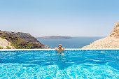 Horizontal color rear view image of woman relaxing in a infinity pool at the resort spa and looking at view.