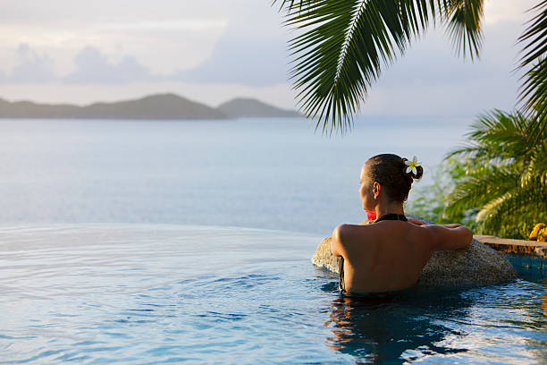 woman in a infinity pool hot tub at the resort spa beautiful woman in a infinity pool hot tub at the Caribbean resort spa infinity pool stock pictures, royalty-free photos & images