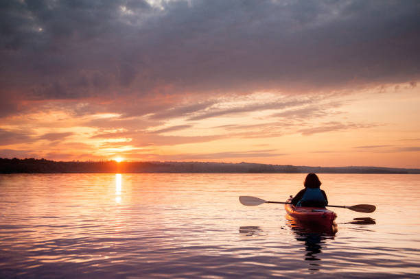 Woman in a kayak on the river on the scenic sunset Woman in a kayak on the river on the scenic sunset lake stock pictures, royalty-free photos & images
