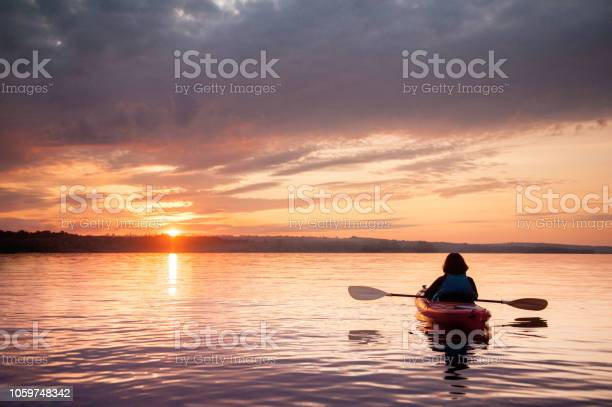 Photo of Woman in a kayak on the river on the scenic sunset