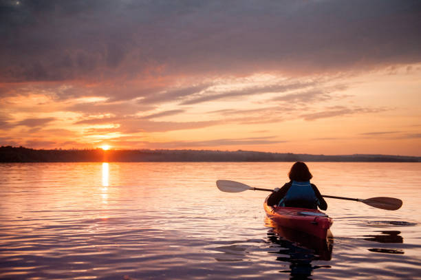 Woman in a kayak on the river on the scenic sunset stock photo