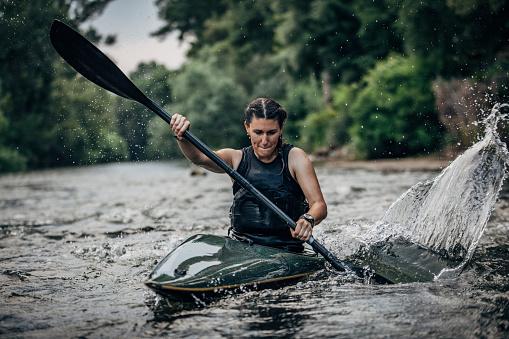 Whitewater kayaking, extreme kayaking. Woman in a kayak sails on a mountain river