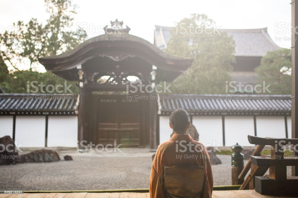 Woman in a Kimono sat peacefully at a Japanese temple stock photo