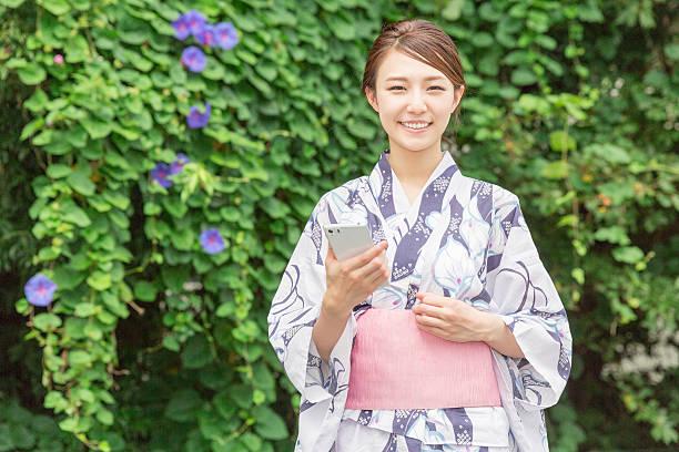 woman in a kimono using a smartphone - kimono ストックフォトと画像